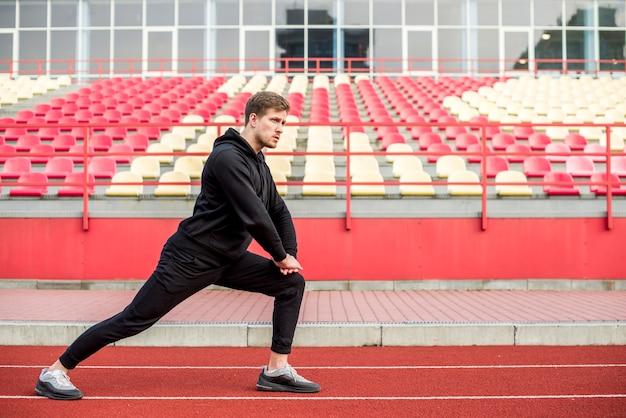 Joven atleta masculino calentando en el estadio Foto gratis