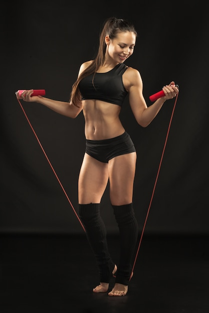 Joven atleta musculoso con una comba en negro Foto gratis