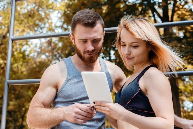 Joven atlética y barbudo, navegar por internet en tablet pc mientras hace ejercicios de fitness en el parque en el día de otoño. Foto Premium