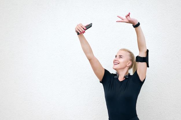 Joven atractiva chica deportiva vistiendo ropa deportiva negra escuchando música y estirando sobre fondo de pared blanca Foto Premium
