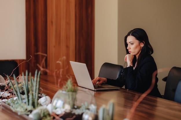 Joven atractiva chica emocional en ropa de estilo empresarial sentado en un escritorio en una computadora portátil y teléfono en la oficina o auditorio Foto Premium