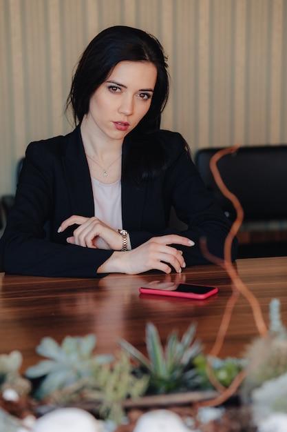 Joven atractiva chica emocional en ropa de estilo empresarial sentado en el escritorio con teléfono en la oficina o audiencia Foto gratis