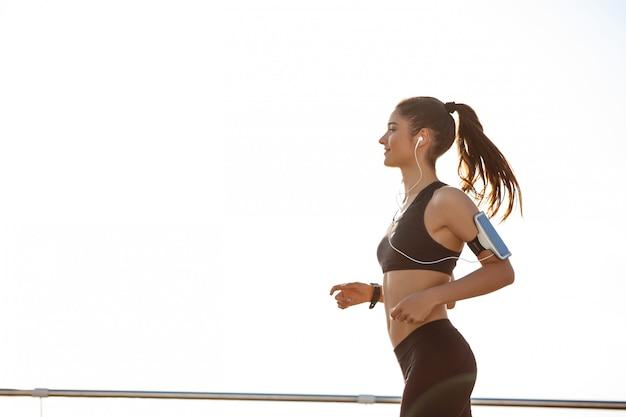 Joven y atractiva chica de fitness trotar junto al mar Foto gratis
