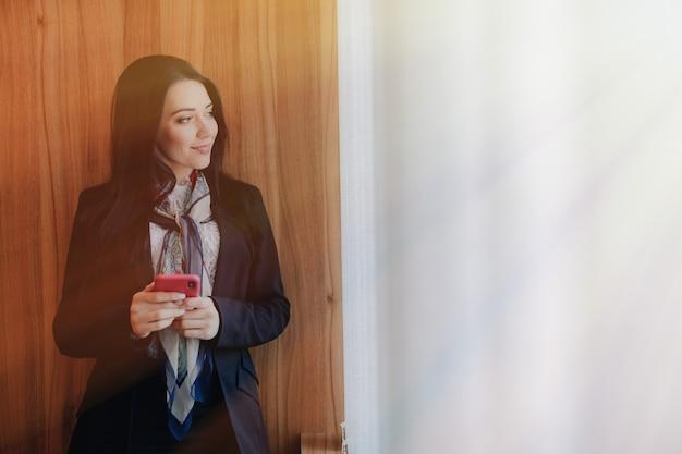 Joven atractiva emocional en ropa de estilo de negocios en una ventana Foto Premium