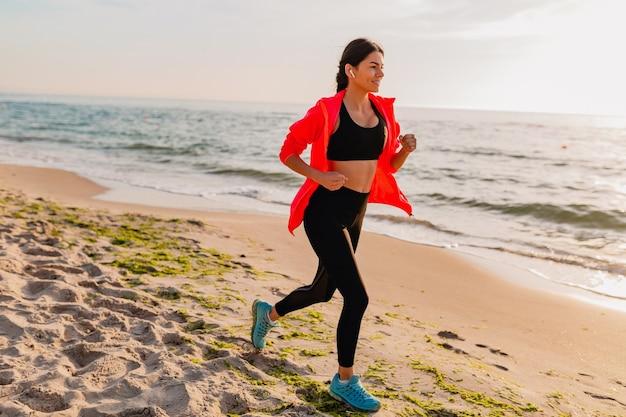 Joven y atractiva mujer delgada haciendo ejercicios deportivos en el amanecer de la mañana trotando en la playa del mar en ropa deportiva, estilo de vida saludable, escuchando música en auriculares, con chaqueta cortavientos rosa Foto gratis