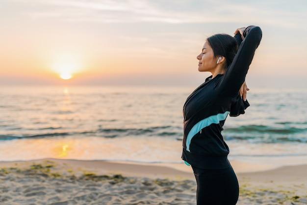 Joven y atractiva mujer delgada haciendo ejercicios deportivos en la playa del amanecer de la mañana en ropa deportiva, estilo de vida saludable, escuchando música en auriculares, haciendo estiramientos Foto gratis