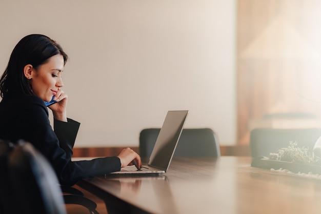 Joven atractiva mujer emocional en ropa de estilo empresarial sentado en el escritorio con una computadora portátil Foto Premium