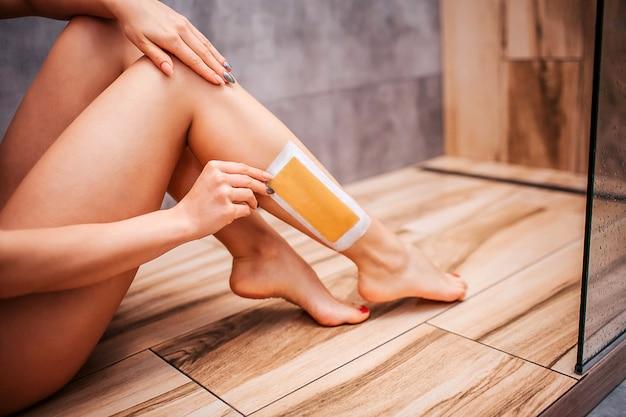 Joven atractiva mujer sexy en la ducha. corte la vista del cuerpo desnudo de la modelo sentado en el piso de madera y haciendo la depilación sola. Foto Premium