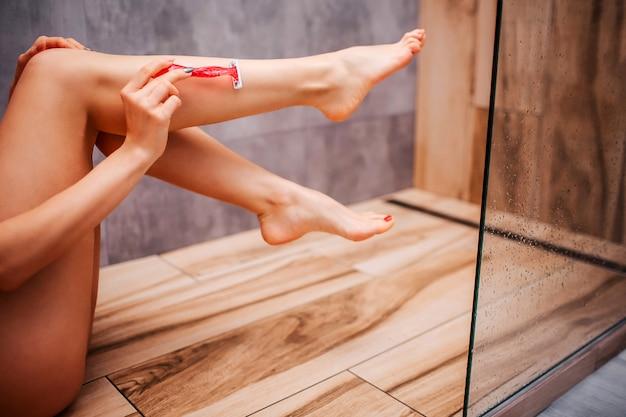 Joven atractiva mujer sexy en la ducha. cuerpo desnudo hermosas piernas bien construidas y deportivas. ella los afeita con navaja y posa. ducha seca. piernas en el aire. vista de corte Foto Premium