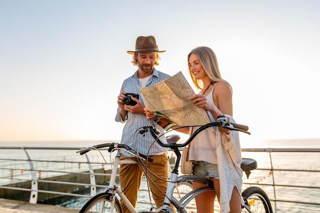 Joven atractivo y mujer viajando en bicicletas con mapa, traje de estilo hipster, amigos divirtiéndose juntos, haciendo turismo tomando fotos en la cámara, pareja en vacaciones de verano en el mar al atardecer Foto gratis