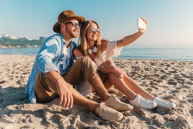 Joven atractivo sonriente feliz hombre y mujer con gafas de sol sentado en la playa de arena tomando selfie foto Foto gratis