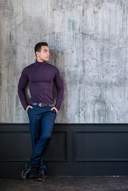 Un joven atractivo con sus manos en el bolsillo apoyado en una pared gris de concreto Foto gratis