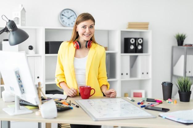 Una joven en auriculares se encuentra cerca de una mesa con una taza roja en sus manos. antes de que la niña en la mesa sea un tablero magnético Foto Premium