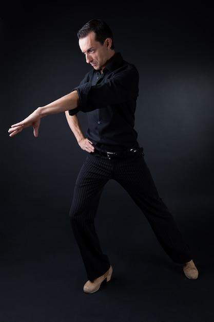 Joven bailarina de flamenco en hermoso vestido sobre fondo negro. Foto gratis