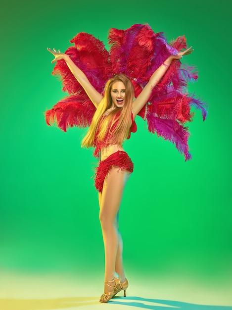 Joven bailarina hermosa posando en la pared verde Foto gratis