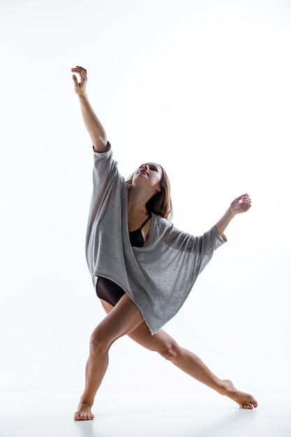 Joven bailarina hermosa en vestido beige bailando en la pared blanca Foto gratis
