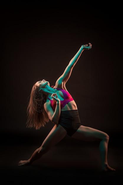Joven bailarina hermosa en vestido beige bailando en la pared negra Foto gratis