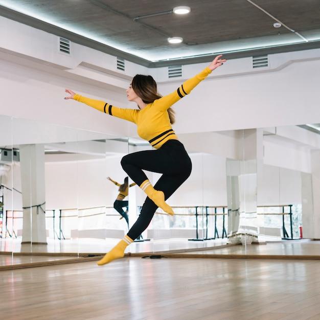 Joven bailarina practicando en el estudio de baile Foto gratis
