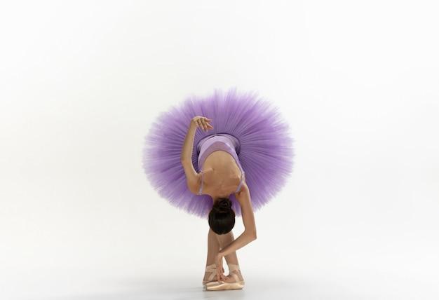 Joven bailarina tierna elegante en la pared blanca Foto gratis
