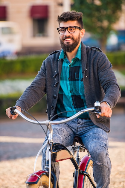 Un joven con barba, camina por la ciudad en bicicleta Foto Premium