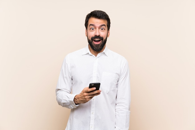 Joven con barba sosteniendo un móvil con expresión facial sorpresa Foto Premium
