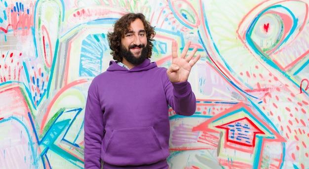 Joven barbudo loco sonriendo y mirando amigable, mostrando el número cuatro o cuarto con la mano hacia adelante, contando en la pared de graffiti Foto Premium