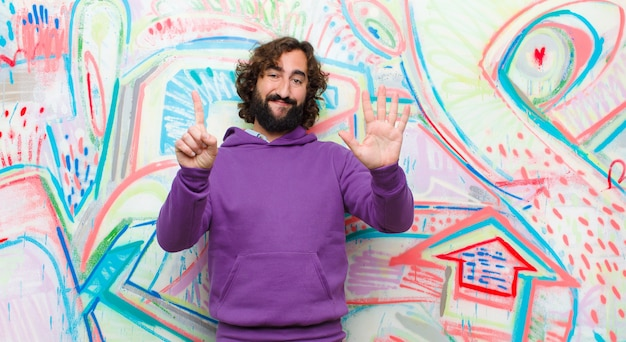 Joven barbudo loco sonriendo y mirando amigable, mostrando el número seis o sexto con la mano hacia adelante, contando en la pared de graffiti Foto Premium