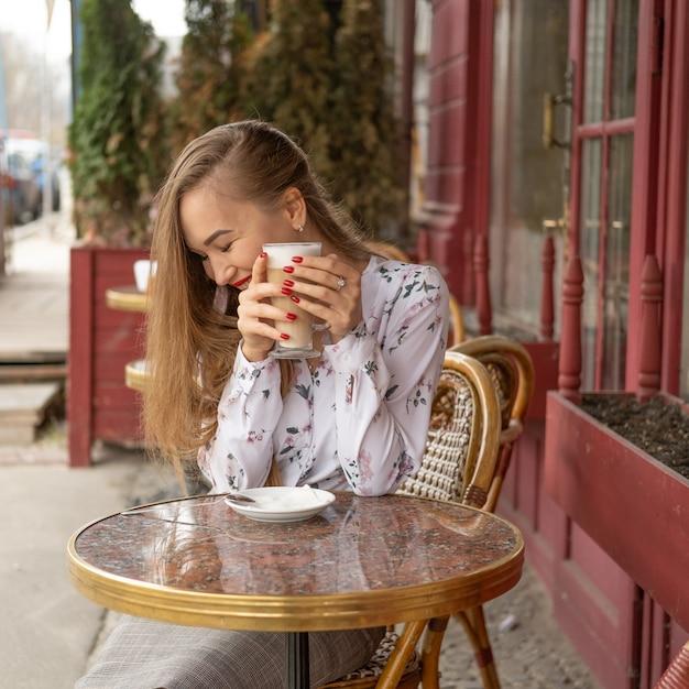Joven bebiendo café en un café parisino de la calle Foto Premium