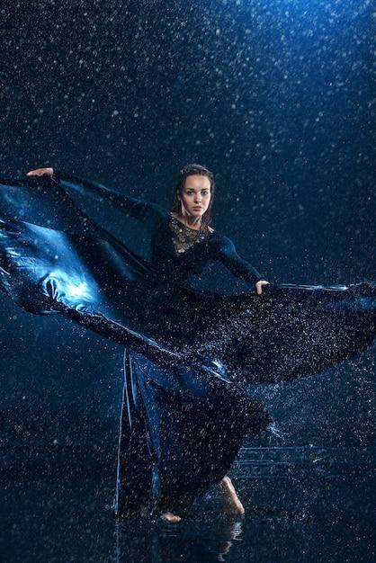 Joven y bella bailarina moderna bailando bajo gotas de agua Foto gratis