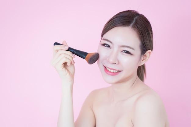 Joven y bella mujer asiática caucásica sonrisa aplicando maquillaje natural en polvo cepillo cosmético Foto Premium