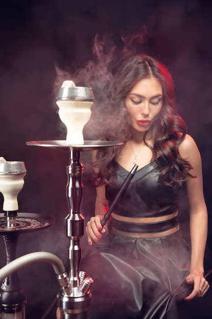 Joven y bella mujer en el club nocturno o bar fuma una cachimba o shisha Foto Premium