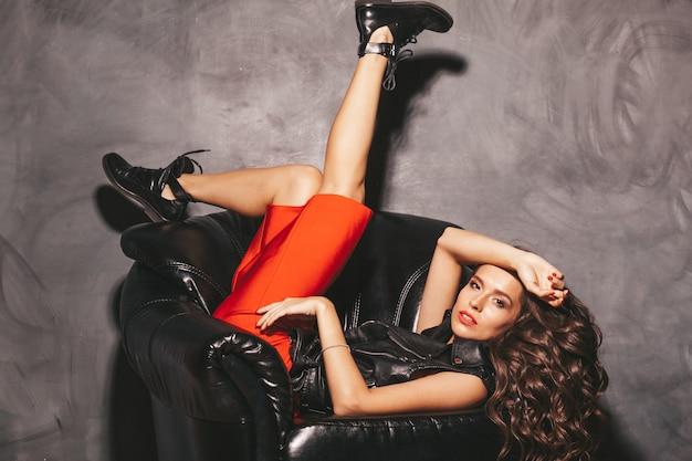 Joven y bella mujer en falda roja de verano de moda y chaqueta de cuero negro. Foto gratis