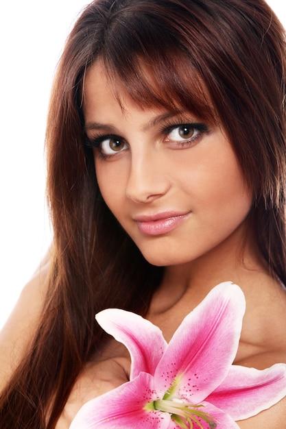 Joven y bella mujer con flor de lirio Foto gratis