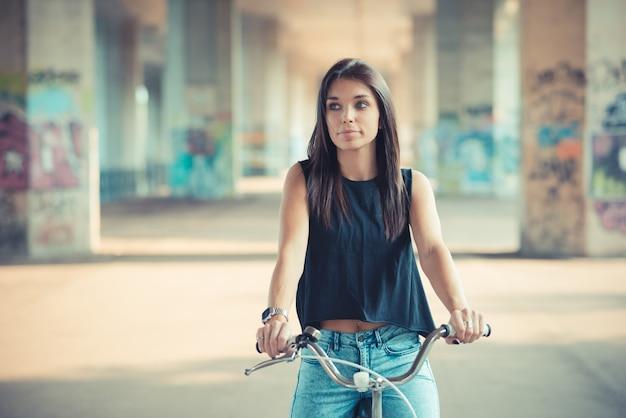 a677a521b6 Joven y bella mujer morena de pelo lacio con bicicleta