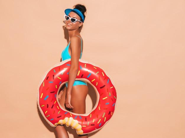 Joven y bella mujer sexy hipster sonriente en gafas de sol. chica en traje de baño de verano con colchón inflable donut lilo. mujer positiva volviéndose loca. pared beige cerca de gorra de visera transparente Foto gratis