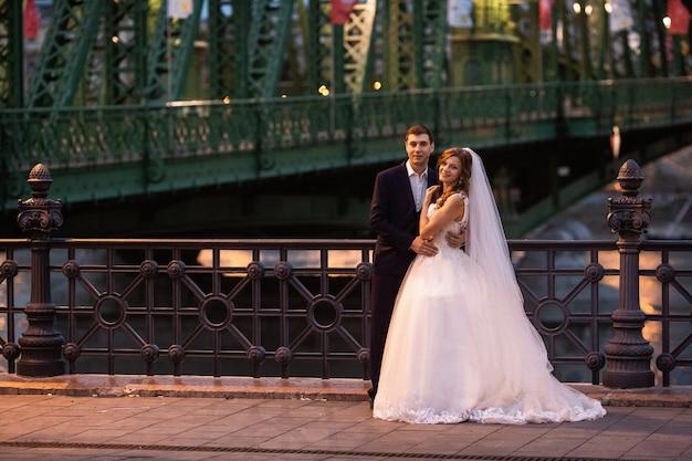 Joven y bella pareja elegante de recién casados cerca del río en budapest Foto Premium