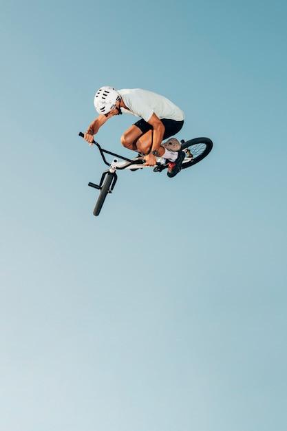 Joven en bicicleta saltando vista de ángulo bajo Foto gratis