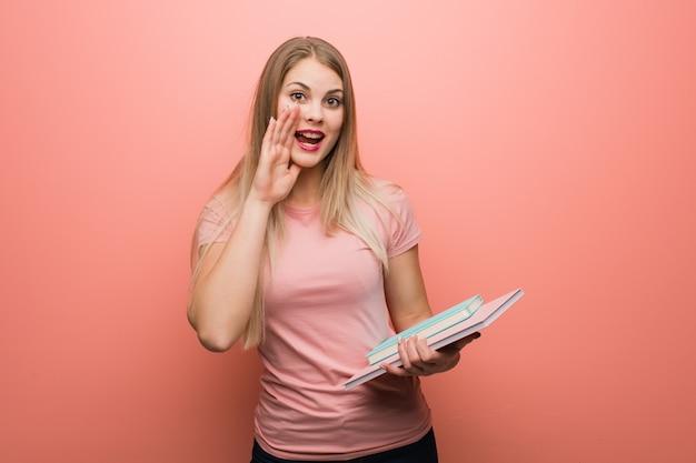 Joven bonita chica rusa gritando algo feliz al frente. ella está sosteniendo libros. Foto Premium