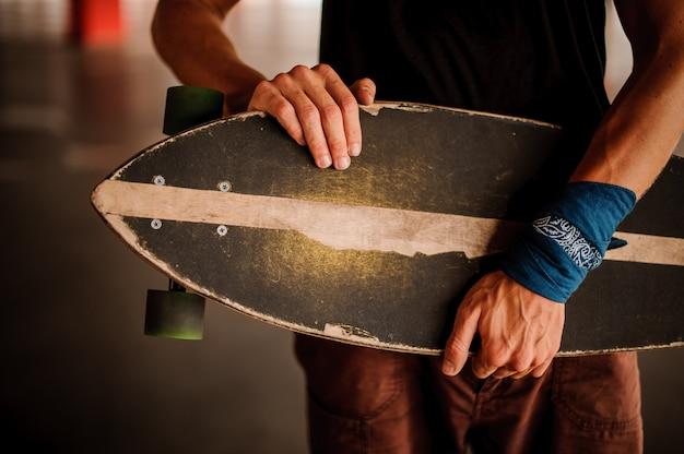 Joven con un brazalete sosteniendo un longboard Foto Premium