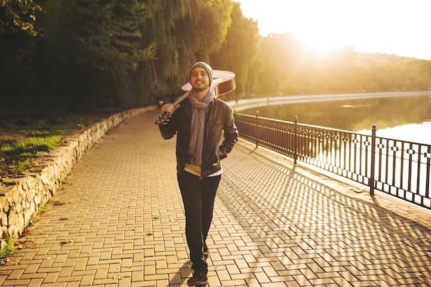 Joven camina por el lago y sosteniendo la guitarra Foto gratis