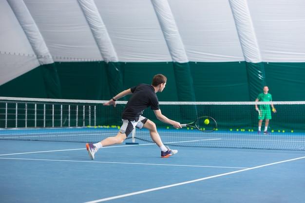 El joven en una cancha de tenis cerrada con pelota Foto gratis