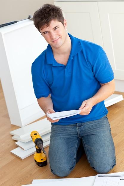 Joven carismático leyendo las instrucciones para armar muebles en la cocina Foto Premium