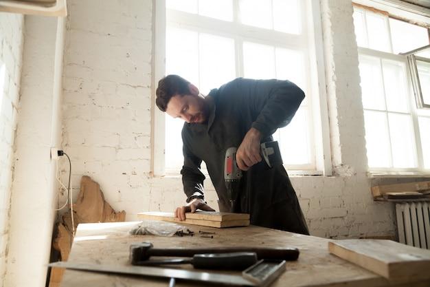 Joven carpintero haciendo carpintería en carpintería Foto Gratis