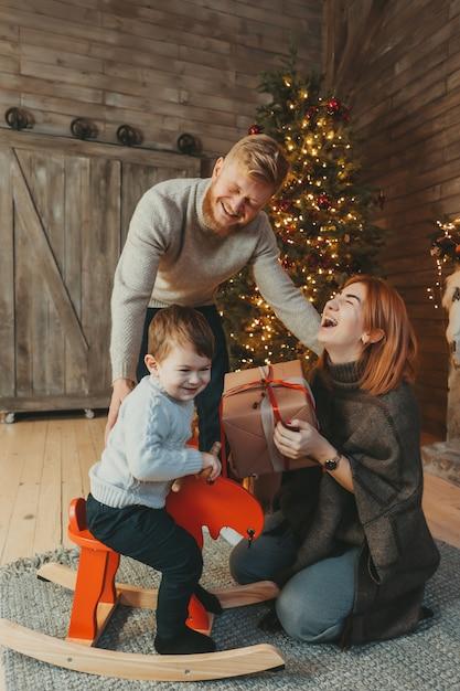 Joven caucásica familia mamá papá hijo cerca de chimenea árbol de navidad Foto gratis