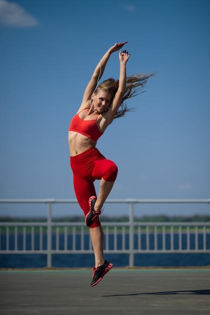 Joven caucásica en ropa deportiva bailando al aire libre Foto Premium