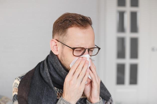 Joven caucásico se resfrió, sonándose la nariz. Foto Premium