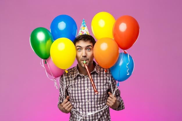 Joven celebrando cumpleaños, sosteniendo globos de colores sobre la pared púrpura. Foto gratis