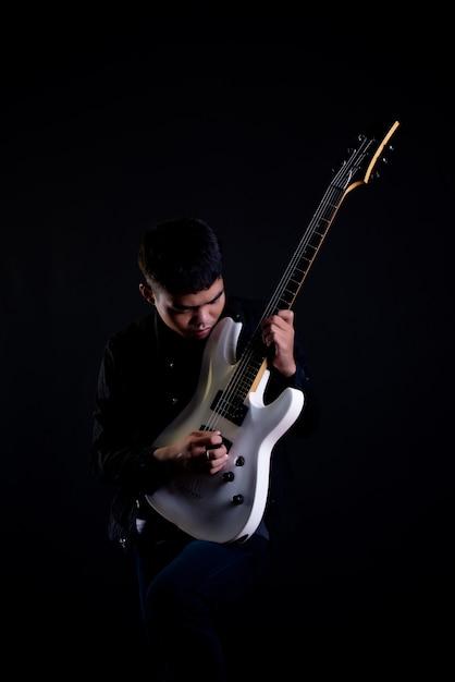 Joven de chaqueta de cuero negro con guitarra eléctrica Foto gratis