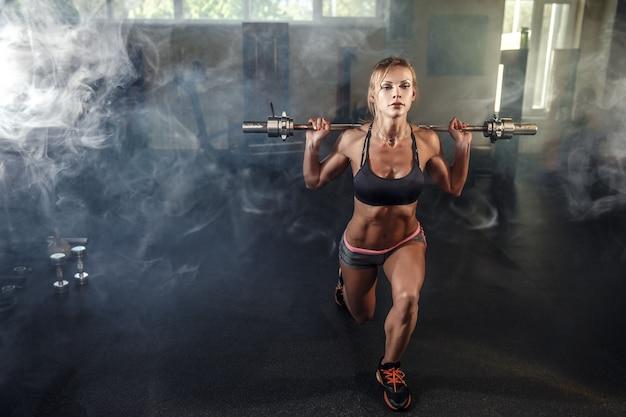 Joven chica sexy en el gimnasio haciendo sentadillas sobre fondo humo Foto Premium