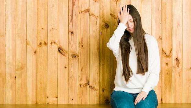Joven china sentada en un lugar de madera olvidando algo, golpeándose la frente con la palma y cerrando los ojos. Foto Premium